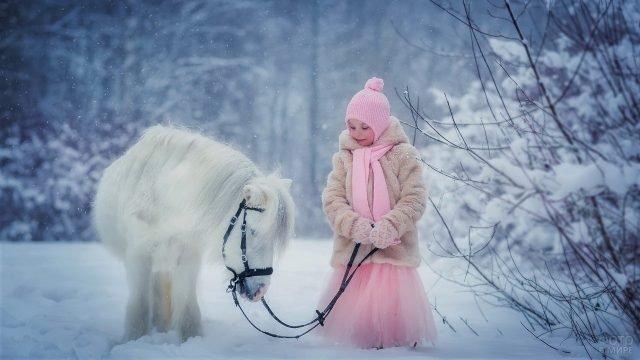 Девочка зимой в розовом платье и шубке с белоснежным пони в лесу