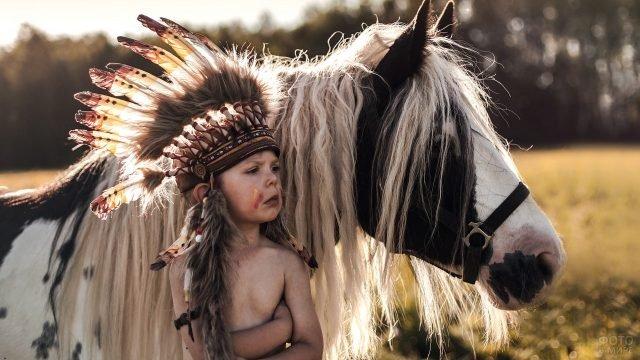 Серьёзный мальчик в костюме индейца стоит рядом с пони