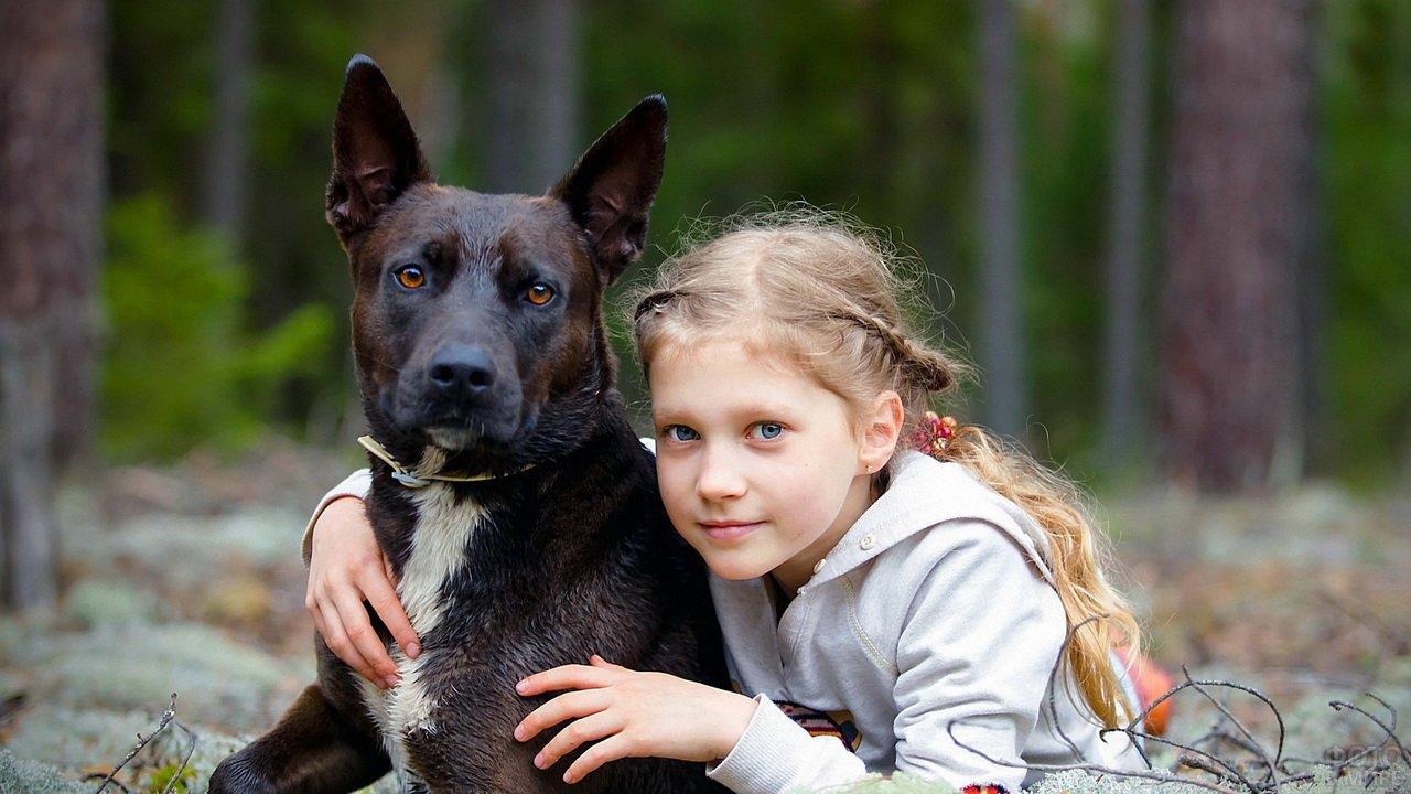 Голубоглазая девочка-блондинка с чёрной собакой