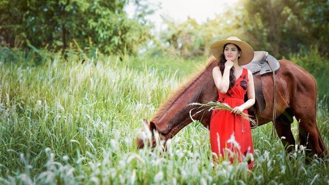 Азиатка в широкополой шляпе с пасущейся на лугу лошадью
