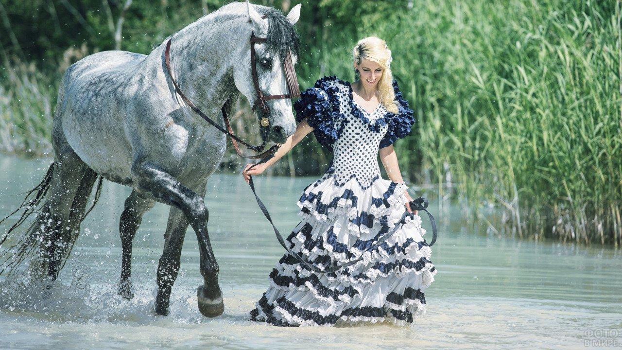 Барышня в длинном платье ведёт коня вброд