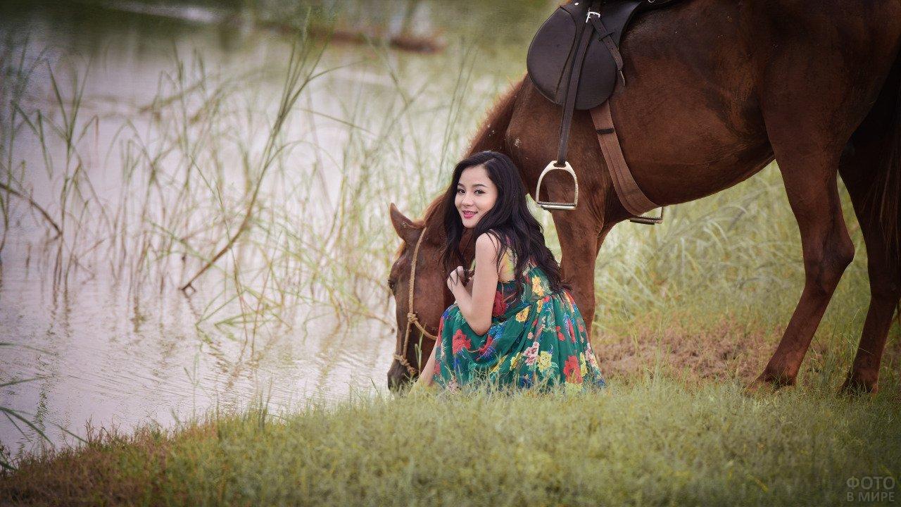 Девушка азиатской внешности с лошадью пьющей из реки