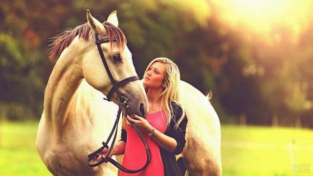 Девушка блондинка и лошадь смотрят друг на друга