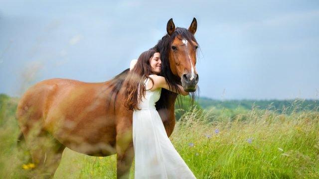 Девушка в белом платье обнимает лошадь среди цветущих трав