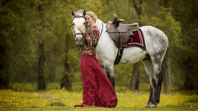 Девушка в длинной юбке и расписном сарафане с белой лошадью