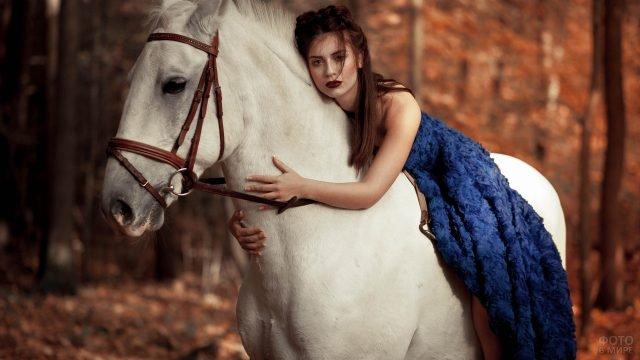 Девушка в синем платье верхом на лошади