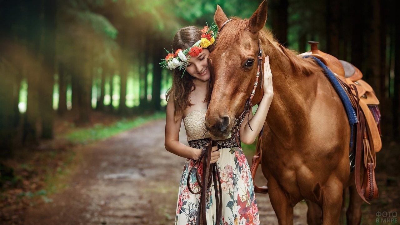 Девушка в венке из цветов обнимает лошадь