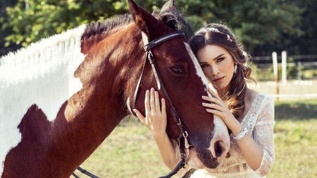 Девушка в воздушном платье обнимает лошадь