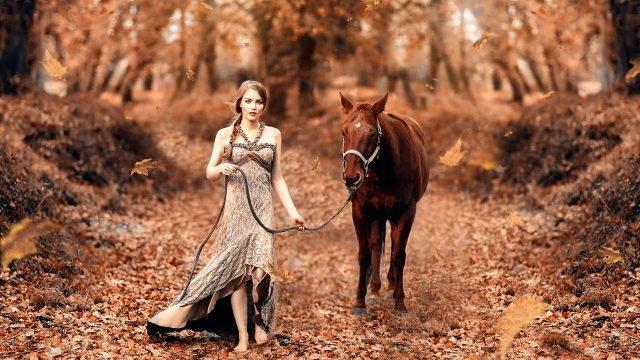 Девушка ведёт коня по осеннему лесу