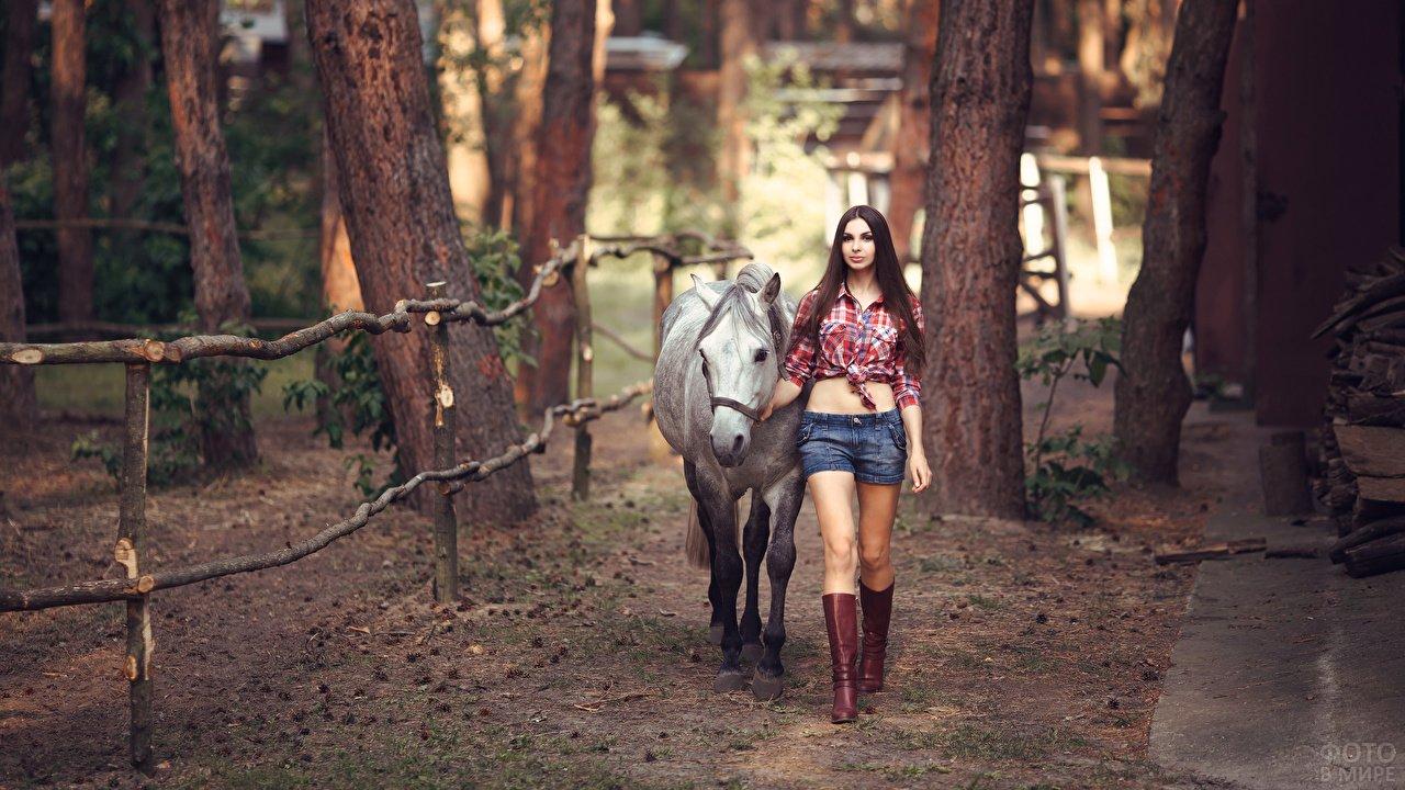 Девушка ведёт лошадь в лесу вдоль загона