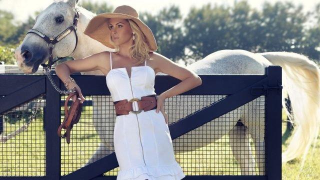 Красивая девушка в широкополой шляпе у ворот загона с лошадью