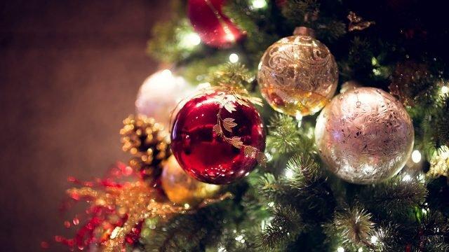 Блестящие ёлочные шары среди огней в новогодний вечер