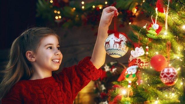 Девочка вешает на новогоднюю ёлку нарядный шарик