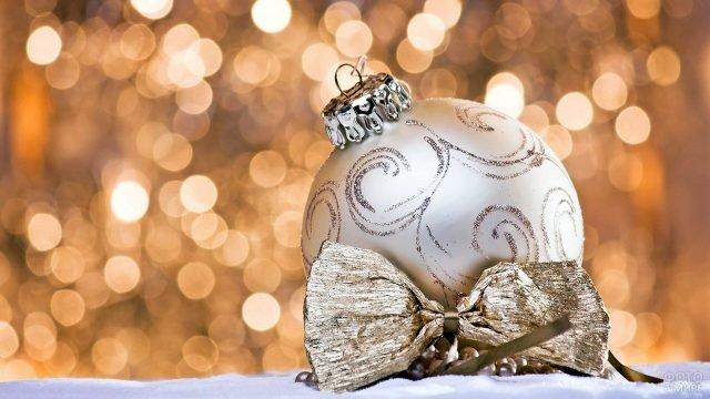 Ёлочный шар и бантик в золотой гамме на фоне новогодних огоньков