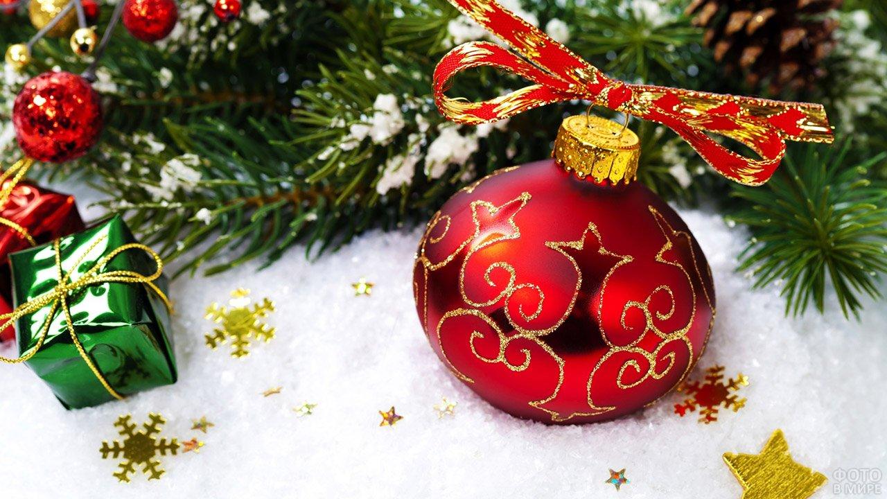 Красный ёлочный шарик с золотым орнаментом на снегу среди новогодних украшений