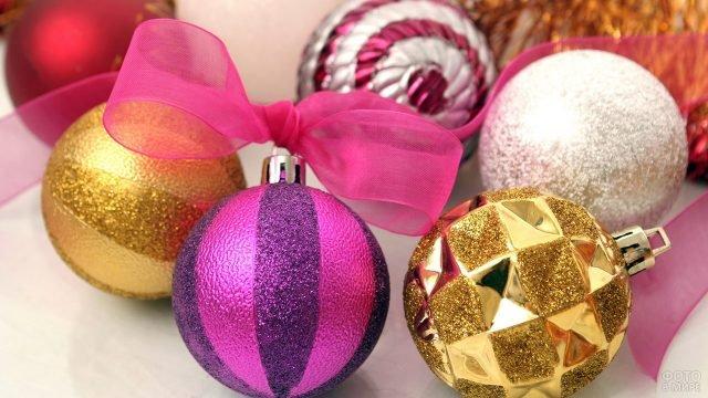 Нарядные ёлочные шарики разных цветов лежат на белом фоне
