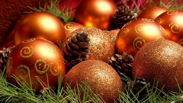 Оранжевые ёлочные шары лежат среди еловых веток и шишек