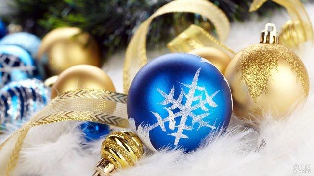 Синие и золотые ёлочные шарики лежат на пушистом белом фоне