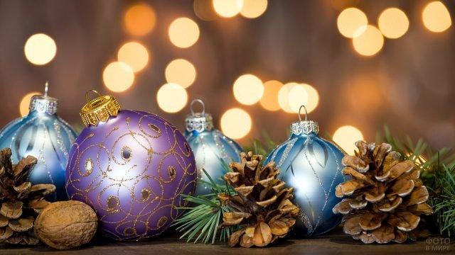 Сиреневые и голубые ёлочные игрушки лежат среди веток и шишек