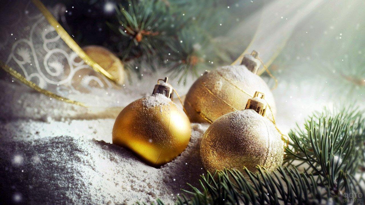 Золотые ёлочные шары лежат на снегу среди еловых веток