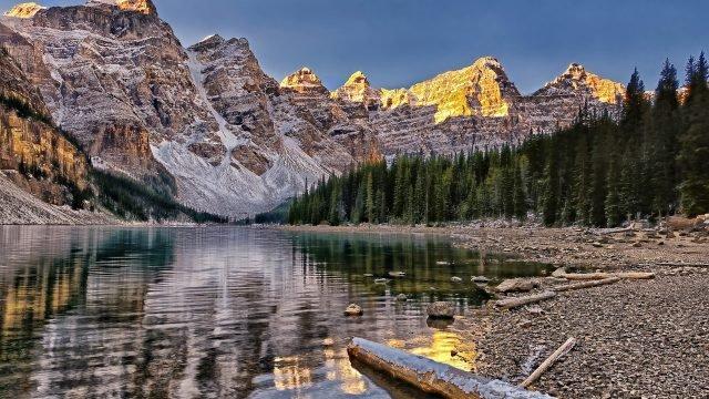 Берег озера на фоне хвойного леса и гор