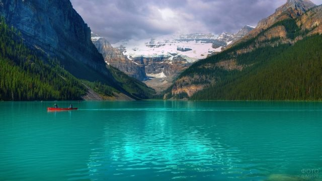 Лодка плывёт по озеру на фоне гор