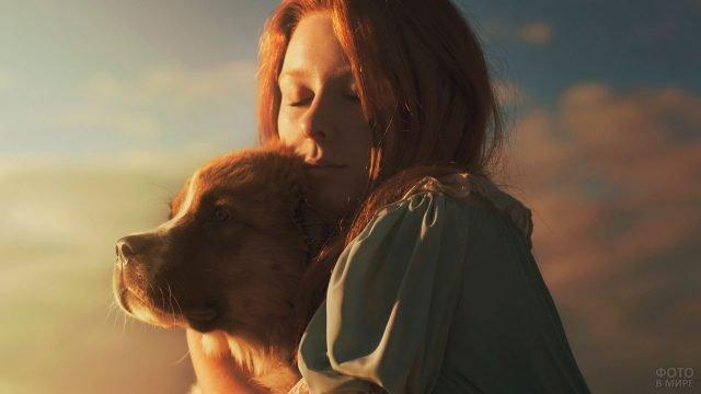 Девушка обнимает большую собаку на закате