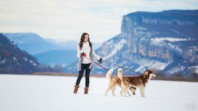 Девушка с двумя хаски в снежных горах