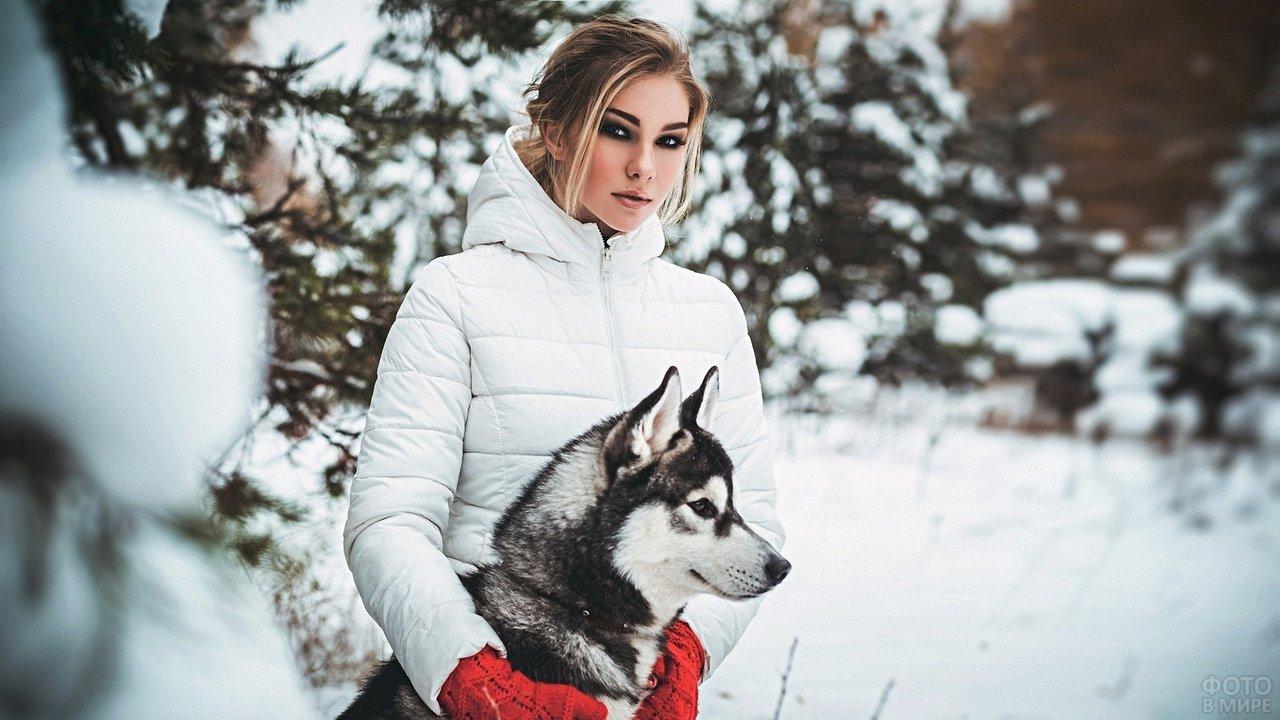 Девушка с красными ворежками держит хаски в зимнем лесу
