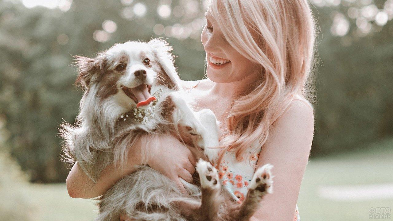Девушка с широкой улыбкой держит на руках маленькую пушистую собаку