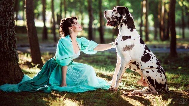Девушка в берюзовом платье с догом в городском парке