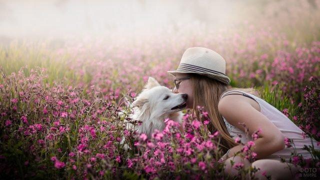 Девушка в шляпе целует белую собаку в цветочном поле