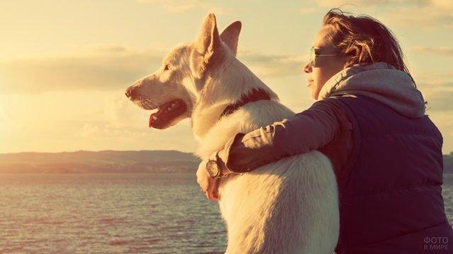 Девушка в солнечных очках обнимает белую собаку на закате