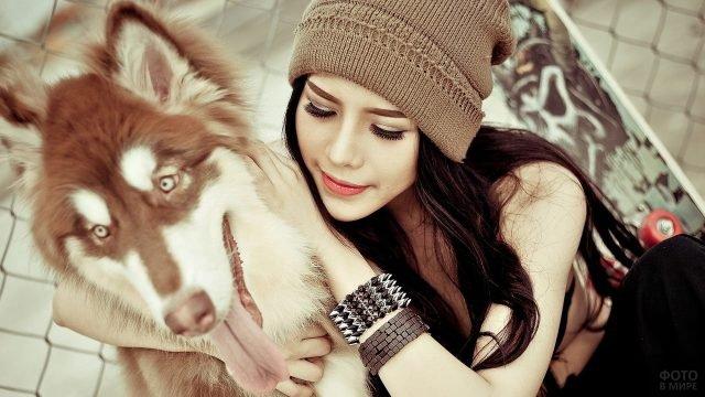 Девушка в вязаной шапке обнимает рыжую собаку