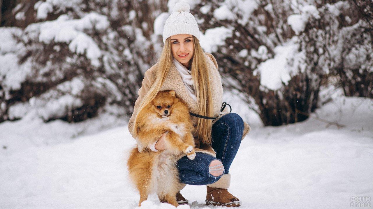 Девушка в зимнем лесу с маленьким рыжим шпицем