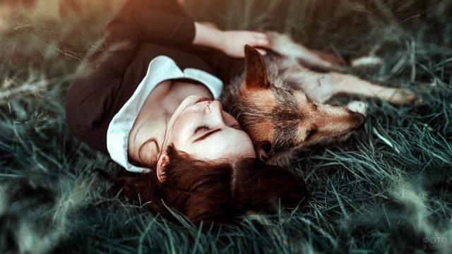 Рыжая девушка лежит на траве с рыжей собакой