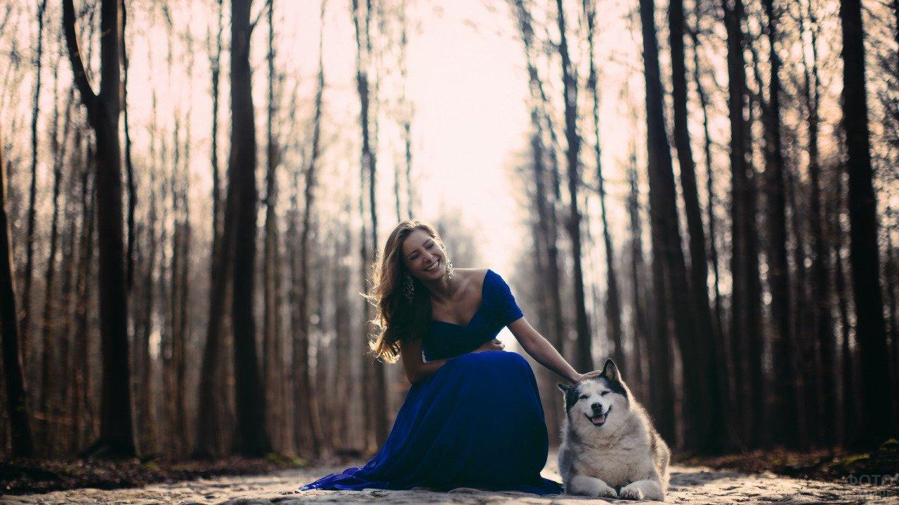 Весёлая девушка в синем платье гладит улыбающуюся собаку