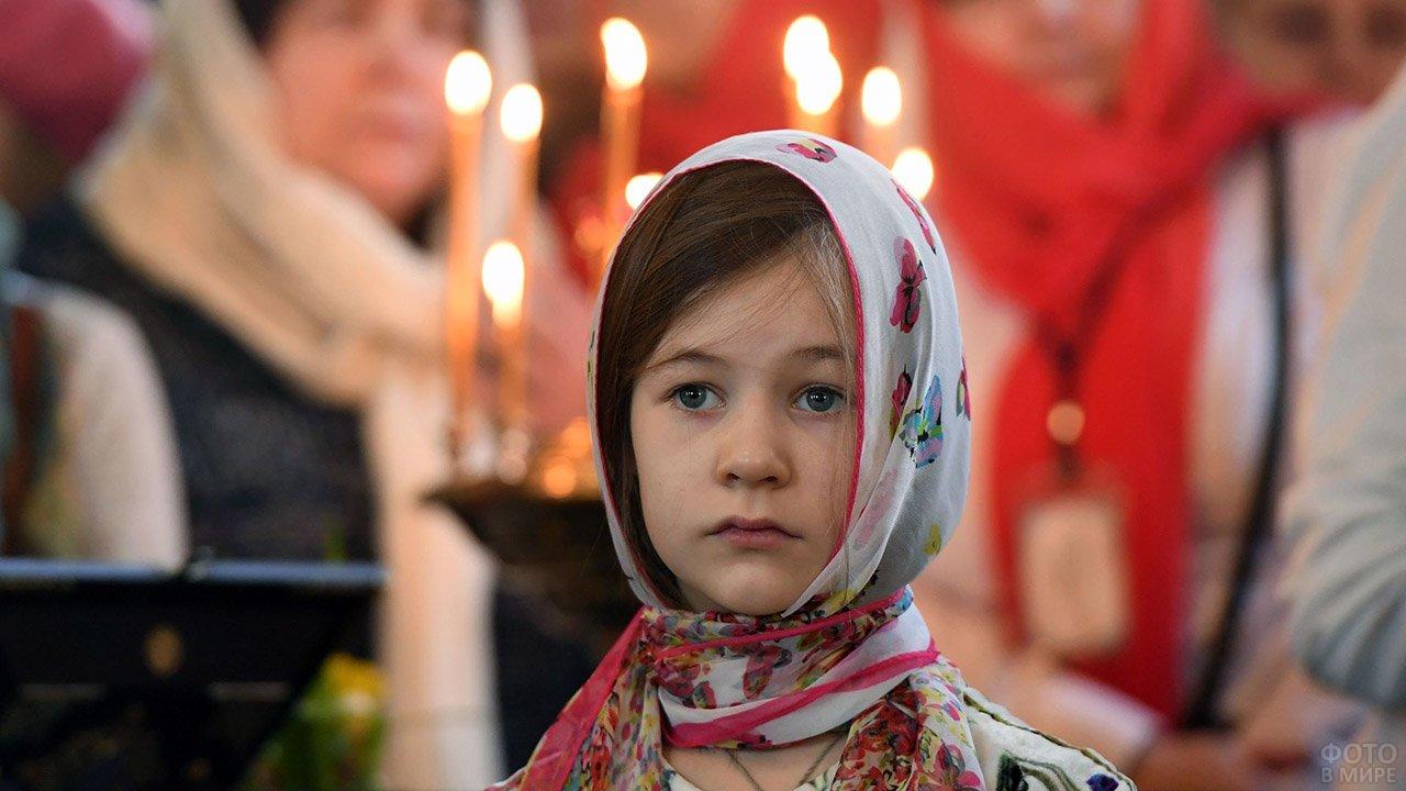 Девочка на фоне свечей в церкви в Прощёное воскресенье