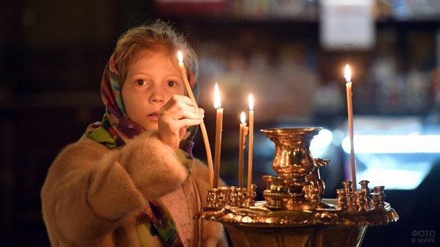 Девочка ставит свечу в Прощёное воскресенье в московском храме