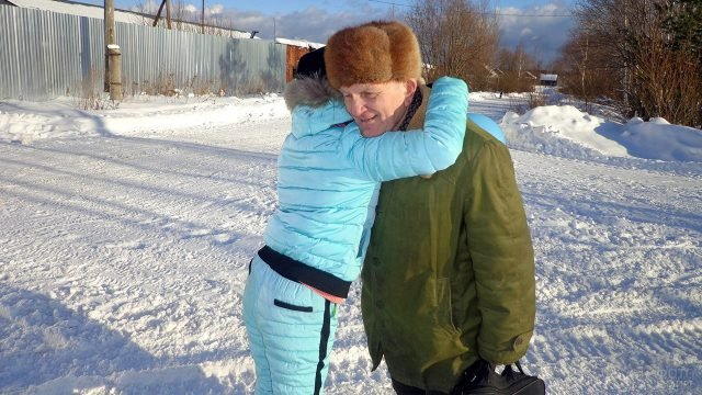 Девушка обнимает деда в Прощёное воскресенье на заснеженной улице
