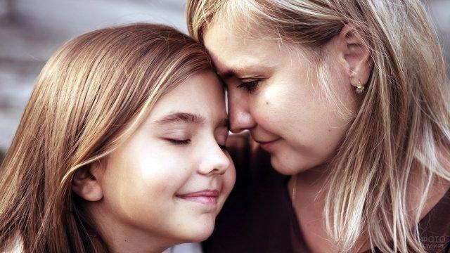 Дочь извиняясь прижимается лбом ко лбу грустной мамы