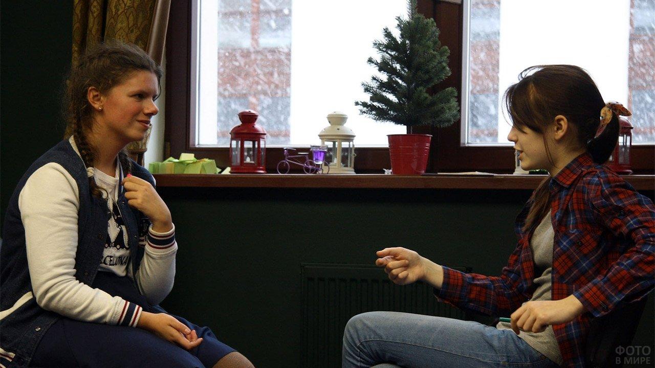 Две девочки-подростка разговаривают после ссоры на фоне снегопада за окном