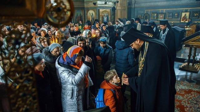 Мальчик впереди других прихожан церкви в Прощёное воскресенье