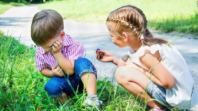 Маленькая девочка протягивает цветочек обидевшемуся мальчику