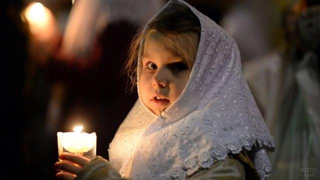 Маленькая девочка со свечой в руках в храме в Прощёное воскресенье