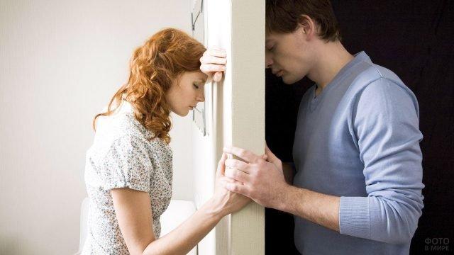 Молодая пара держатся за руки на пороге взаимного прощения