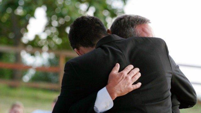 Отец крепко обнимает извинившегося взрослого сына