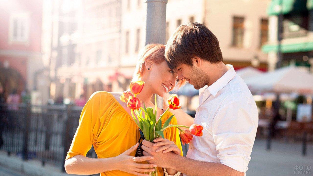 Помирившаяся парочка на солнечной улице с букетом цветов