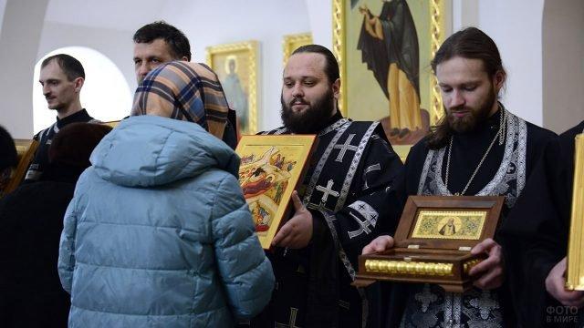 Прихожанка перед служителями церкви во время Чина Прощения