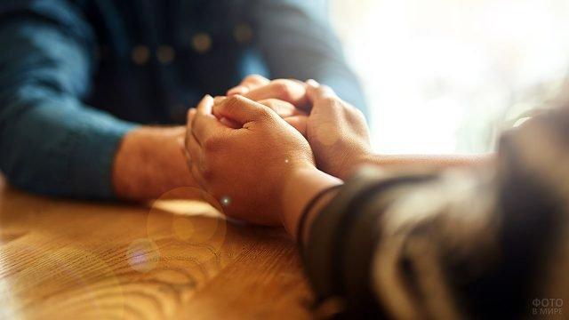 Руки просящего прощения обнимают сжатые кулаки обиженного